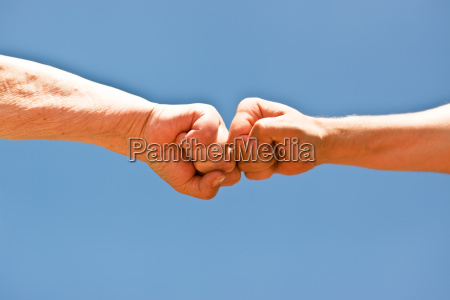 two fists against a blue sky
