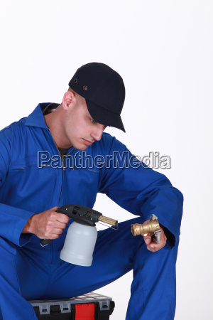 plumber using blow torch on brass