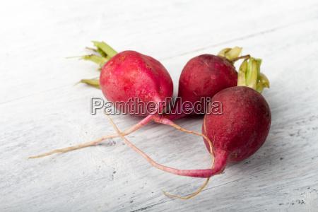three radishes on wood