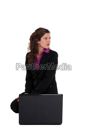 attractive young businesswoman crouching with laptop