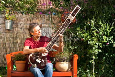 elderly man sitting in his garden