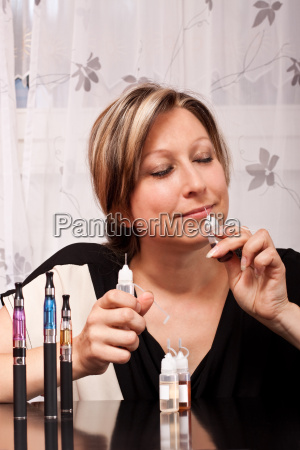blonde young woman smelling liquid for