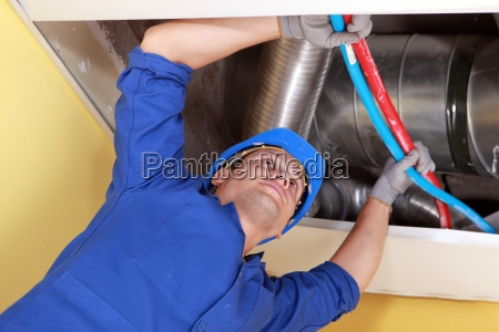 worker holding blue and red pipes