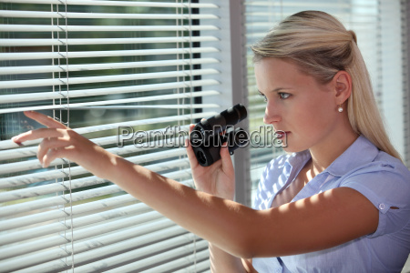 woman looking through the blinds with
