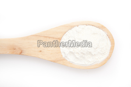 wooden spoon with flour against a