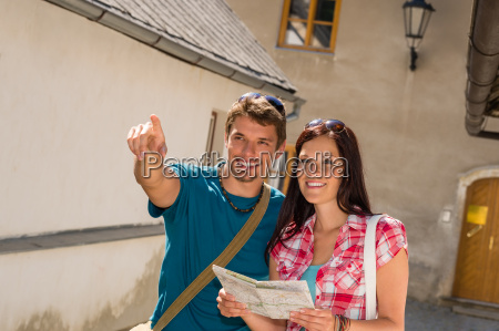 young couple in city man pointing