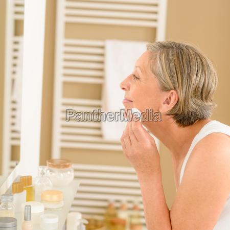 cara limpia mujer senior con algodon