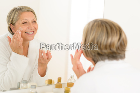 mature woman apply cream looking bathroom