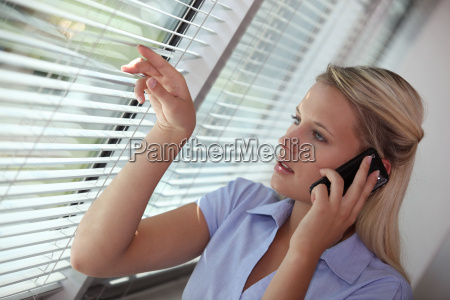 businesswoman peering through blinds during call