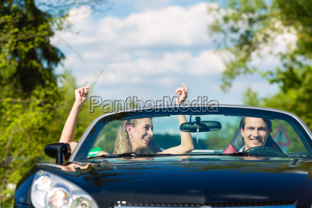 young couple with convertible in summer