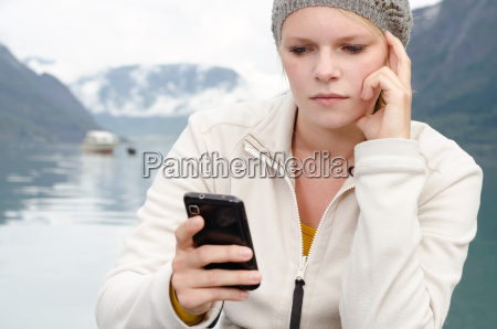 young blond woman with her smartphone