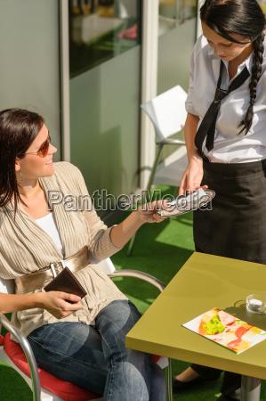 woman paying bill to waitress cafe