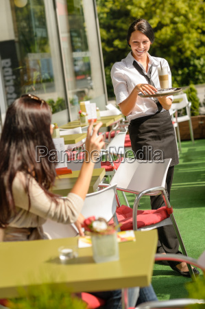waitress bringing woman coffee order restaurant
