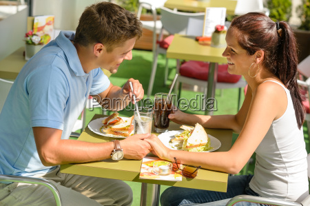 couple holding hands flirting at cafe