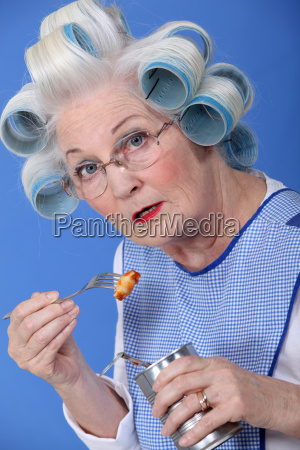 funny grandmother eating canned food with