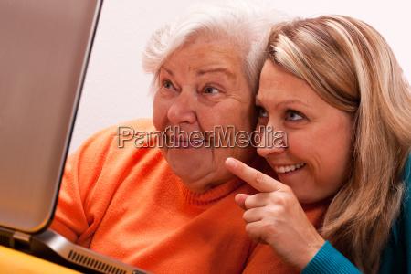 seniorin and young woman sit at