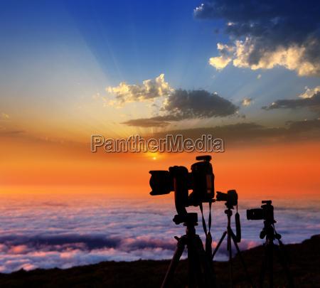 camera tripods photographer sunset sea of