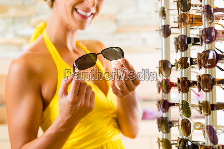 young woman at the optician buys