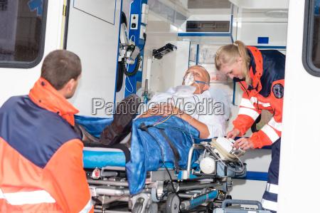 paramedics putting patient in ambulance car