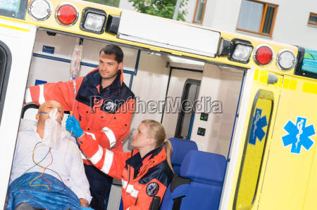paramedics checking iv drip patient in