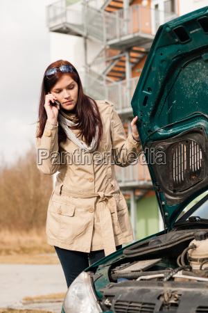 woman looking under car hood on