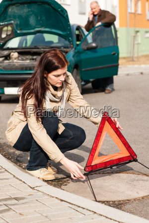 woman putting triangle sign for car