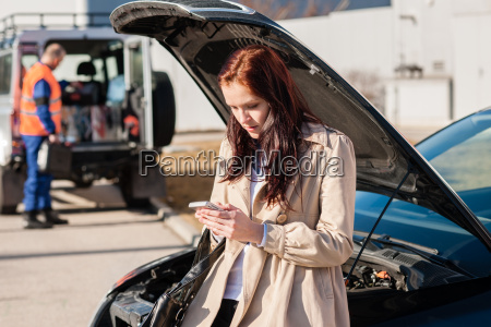 woman dialing her phone after car