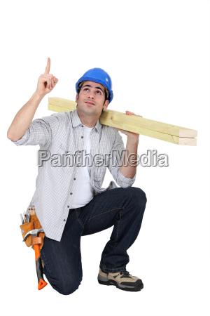 carpenter kneeling and pointing upwards