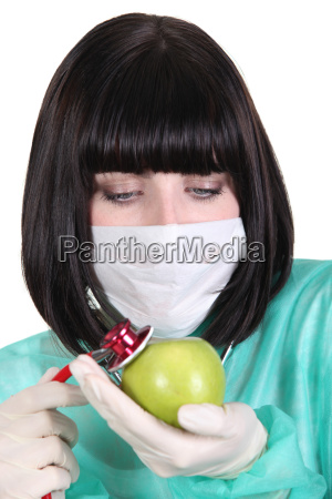 nurse examining an apple with a
