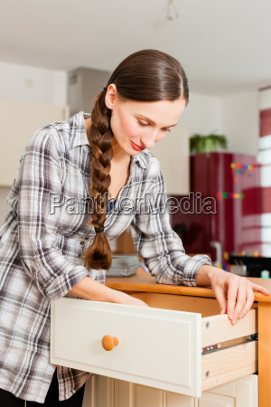 young woman builds on cabinet or