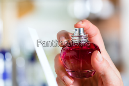 young woman buying perfume in perfumery