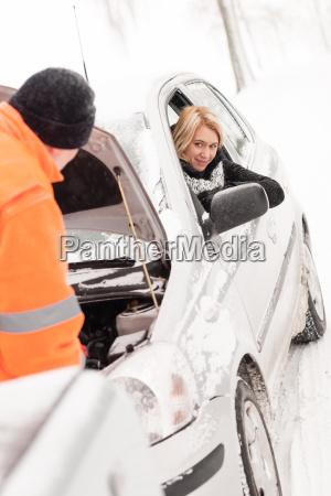 man repairing womans car snow assistance