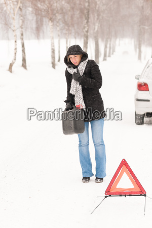 woman walking with gas can car