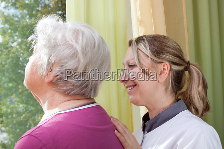 senior and nurse stand at the