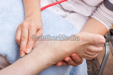 doctor examines patients foot