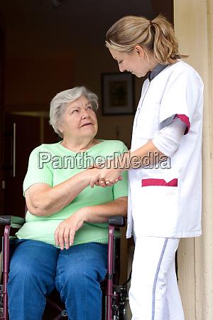 nurse hands patient in wheelchair her