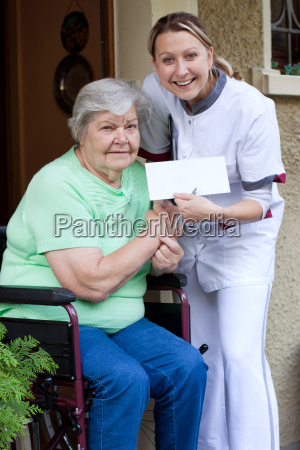 nurse and patient in wheelchairhold together