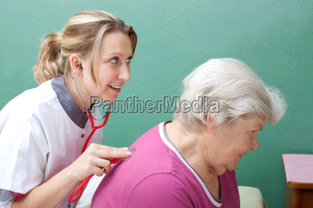 female doctor examines patient with a