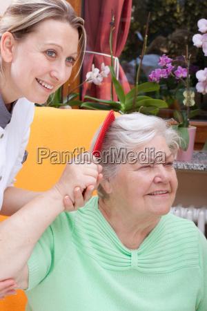 nurse combs a senior womans hair
