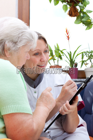 senior and nurse sit together and