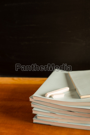 academical notepads and chalks on wooden