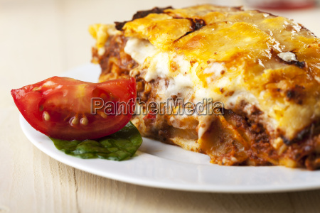 lasagna on a plate with tomato