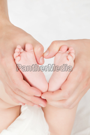 mother hands holding baby feet