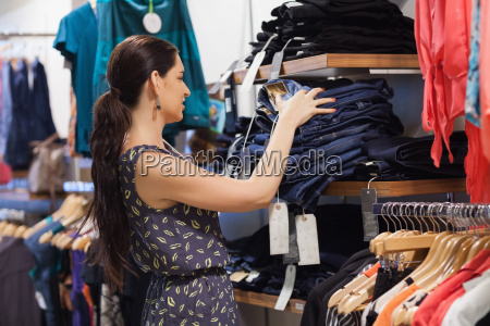 woman stacking jeans on shelf in