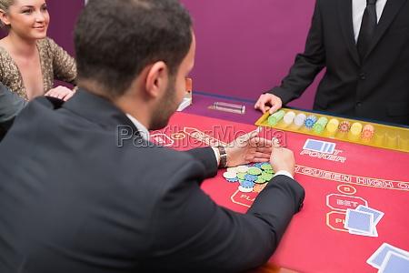 man taking his prize at poker
