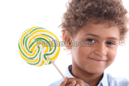 little boy holding lollipop