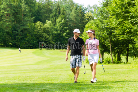 young sporty couple playing golf on