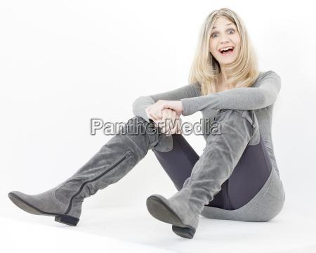 sitting woman wearing fashionable gray boots