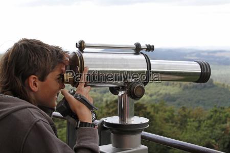 teenager looks through binoculars