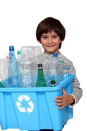 little boy recycling plastic bottles